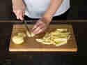 Pommes: Kartoffen auf Holzbrett in Stifte schneiden
