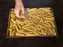 Pommes: Rohe, gewürzte Kartoffelstifte auf Backblech verteilen
