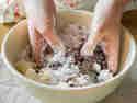 Kuchenkrümel mit Puderzucker, Frischkäse und Butter verkneten