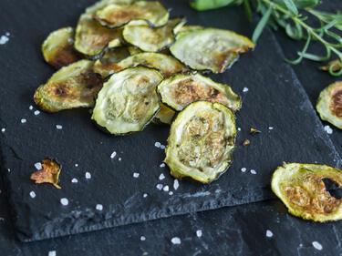 Zucchini Chips mit Basilikum und Rosmarin auf Platte