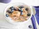 Buchweizen-Blaubeer-Porridge mit Chia-Samen mit Mandelmus und Kokosmilch garniert