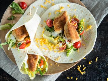 Crispy Chicken Wrap mit Salat, Tomate und Cheddar auf Holzbrett serviert
