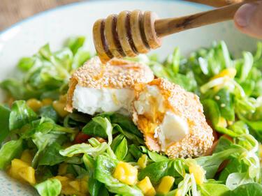 Gebackener Feta auf Feldsalat wird mit Honig beträufelt