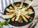 Honigmelone mit Mozzarella, Schinken und Pesto abwechselnd im Kreis auf einem Teller angerichtet