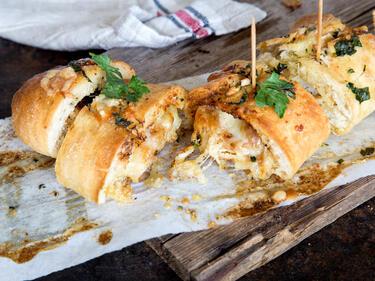 Knuspriges Hähnchen Baguette mit Knoblauchbutter und Mozzarella, angeschnitten auf Holzbrett