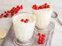 Weiße Mousse au Chokolat in einem Glas serviert, garniert mit roten Johannesbeeren