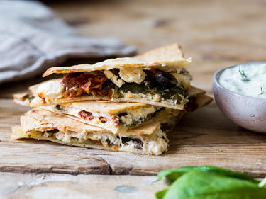Quesadillas mit Feta gestapelt und auf einem Holzbrett serviert