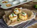 Herzhafte Zwiebelkuchenmuffins werden auf einem Brettchen serviert