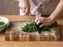Blanchierten Kohl mit dem Messer hacken.