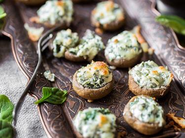 Gefüllte Champignons gefüllt mit Spinat, überbacken mit Mozzarella, serviert auf einer Platte