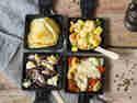 Vier internationale Raclette-Pfännchen.