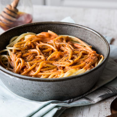 Tomaten-Honig-Sauce auf Spaghetti in einer dunklen Schale