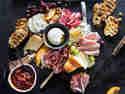 Italienische Vorspeisenplatte - verschiedene italienische Lebensmittel auf einer Holzplatte angerichtet