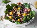 Spinatsalat mit Honig-Senf-Dressing, Hähnchen, Mango und Sonnenblumenkernen in einer Schüssel