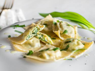 Bärlauch Ravioli mit Zitronenbutter beträufelt und Parmesan bestreut