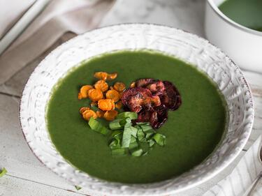 Cremige Bärlauchsuppe mit Gemüsechips im tiefen Teller
