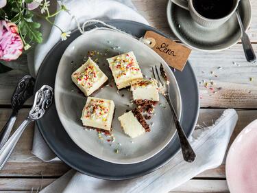 Mehrere kleine weiße Schokohappen mit Schoko-Cookie-Boden und bunten Streuseln auf Teller mit Gabel