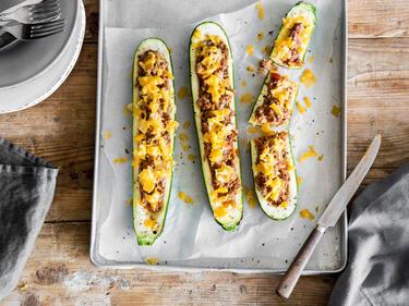 Gefüllte Zucchini mit Hackfleisch und Cheddar auf einem grauen Backblech