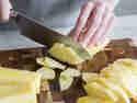 Ananas in mundgerechte Stücke schneiden