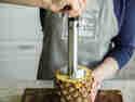 Ananasschneider in die Frucht drehen