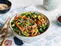 Soba-Nudeln mit buntem Gemüse sind in einer weißen Schüssel angerichtet. Daneben liegen Stäbchen.