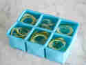 Spiralnudeln in den Kammern einer Eiswürfelform verteilen und mit Wasser aufgießen.