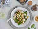 Vollkorn-Tagliatelle mit Spinat und Erbsen in einem Teller mit einem Glas Wein serviert
