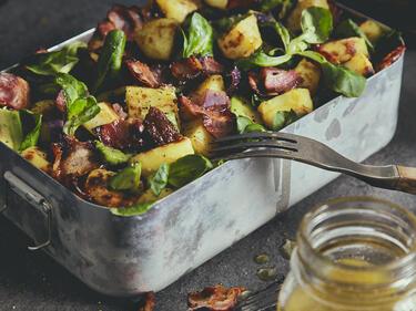 Bratkartoffelsalat mit Bacon-Vinaigrette, serviert in einer Metall-Lunchbox.