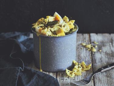 Curry-Nudelsalat mit Spargel ist in einer grauen, hohen Tasse angerichtet