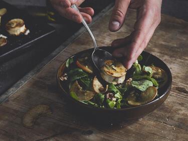 Feldsalat wird mit gegrilltem Ziegenkäse getoppt.