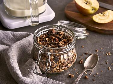 Granola in einem Vorratsglas steht auf einem gedeckten Tisch