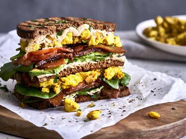 Veganes Frühstückssandwich mit Hummus, Rührtofu und Seitan-Bacon