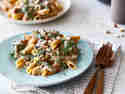 Vegane Vollkornnudeln mit Champignon-Rahmsauce auf einem Teller mit Besteck